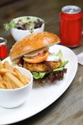 Chicken cajun burger with fresh salad, french fries and condiments Stock Photos