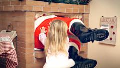 Christmas Eve little girl push Santa Claus in fireplace Stock Footage