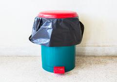 Trash can with a pastic bag inside indoor in front of exposed concrete wall Stock Photos