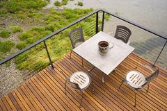 Wood plank deck patio beach water stainless steel dining set Stock Photos