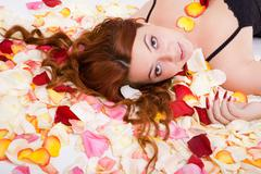 Young sensual woman lying on petal Stock Photos