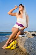 bride in swimsuit on the sea coast - stock photo