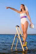 bride in swimsuit in the sea on stairs - stock photo