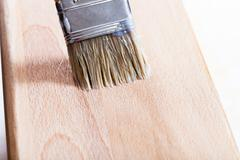 putting varnish on beach wooden board - stock photo
