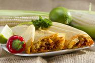 Stock Photo of mexican tamale wrapped in corn husk served on plate.