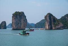 Rocky islands and boats in Halong Bay Stock Photos