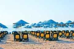 neat rows of sun loungers on the beach - stock photo