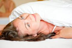 Beautiful girl on the bed in the morning serene vulnerable Stock Photos