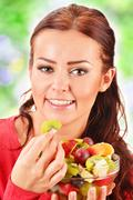 Young woman eating fruit salad Stock Photos