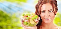 Nuori nainen, jolla lasi kulho hedelmäsalaattia Kuvituskuvat