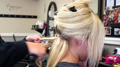 Blonde woman getting hair styled with curling iron Stock Footage