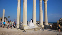 Photographer taking pictures of new-married couple near Temple of Apollo ruines Stock Footage