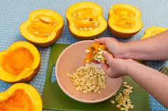A cook extracting the seeds from a pumpkin Stock Photos