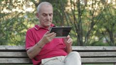 Senior man using tablet computer in park Stock Footage