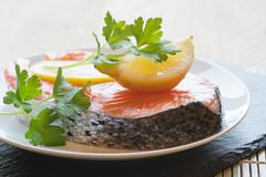 raw fresh salmon cutlet steak with lemon and parsley garnish - stock photo