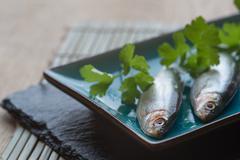 fresh tasty raw sprats on serving dish - stock photo