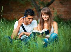 two students studying in park on grass with book outdoors - stock photo