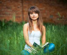 Young girl with book in the park on green grass Stock Photos