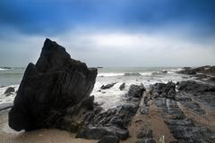 landscape seascape of jagged and rugged rocks on coastline with long exposure - stock photo