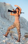 Stock Photo of young female soldier dressed in a camouflage with a gun in the location