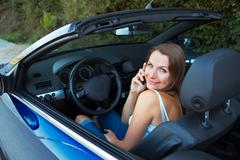 Caucasian woman talking on phone in a cabriolet car - stock photo
