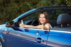 smiling woman showing key in a cabriolet car - stock photo