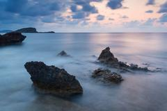 Stunning landscape dawn sunrise with rocky coastline and long exposure mediter Stock Photos