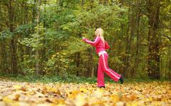 woman running in autumn fall forest. jogging outside. - stock photo