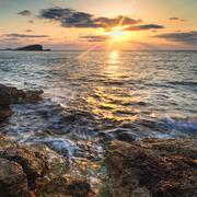 stunning landscape dawn sunrise with rocky coastline and long exposure mediter - stock photo