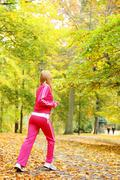 Woman running in autumn fall forest. jogging outside. Stock Photos