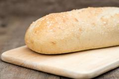 loaf of sourdough bread in rustic kitchend setting - stock photo