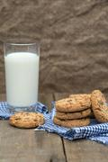 Rustic setting with chocolate chip cookies and glass of milk Stock Photos