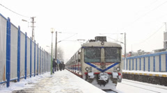 Train leaves the snow covered station Stock Footage