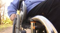 Disabled senior hand turning wheelchair - stock footage