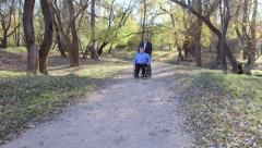 Caregiver walking with disabled senior in wheelchair - stock footage