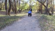 Caregiver walking with disabled senior in wheelchair Stock Footage