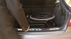Caregiver loading and unloading  wheelchiar in car trunk Stock Footage