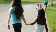 Big Sister And Little Sister Hold Hands, Walk Through Park Stock Footage