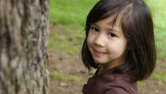 Cute Little Girl Smiles, Walks Around Tree Stock Footage