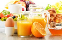 Breakfast with coffee, orange juice, croissant, egg, vegetables and fruits Stock Photos