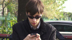 Attractive young man using a smartphone  on a bench, urban scene Stock Footage