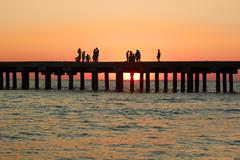 people on the old sea pier during sunset - stock photo