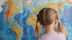 Little girl showing Indian ocean on a geographical map - stock footage