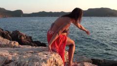 Pregnant in dhoti skirt leaves seaside - stock footage