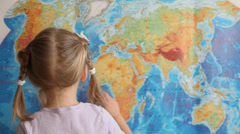 Little girl showing Atlantic Ocean and Indian ocean on a geographical map Stock Footage