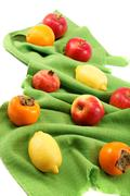 Stock Photo of set of different fresh fruits on green cloth.