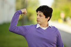 Weak man flexing his muscles - stock photo