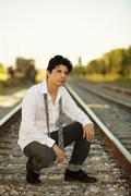 Man posing on railroad tracks Stock Photos