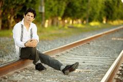 Man posing on railroad tracks - stock photo