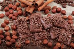 Chocolate, hazelnut, coffee and cinnamon sticks with cloth on a wooden table. Stock Photos